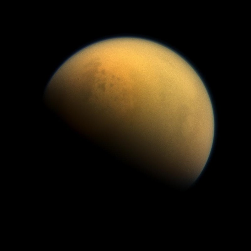 Saturn's largest moon Titan has a thick, smoggy atmosphere and is home to vast lakes of liquid methane, which are visible in this image as darker blotches in the moon's upper right