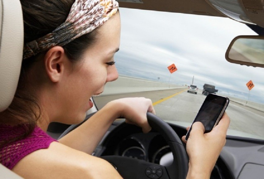 woman on smartphone in car while driving 640x435